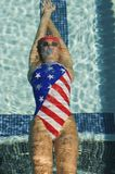 Participant Swimming In A Backstroke. High angle view of female participant in a American swimsuit swimming in backstroke Royalty Free Stock Images
