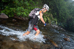 Participant wading through river in race Stock Image