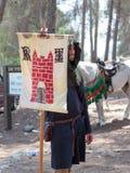 Participante en la reconstrucción de cuernos del soporte de la batalla de Hattin en 1187 con la bandera del rey de Jerusalén en e Imagen de archivo libre de regalías