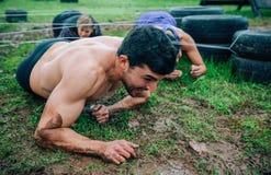 Participante masculino em um rastejamento do curso de obstáculo imagem de stock royalty free