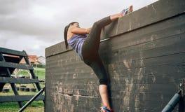 Participante na parede de escalada do curso de obstáculo foto de stock
