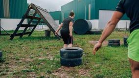 Participante nas rodas de arrasto de um curso de obstáculo fotografia de stock