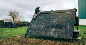 Participante no obstáculo de escalada da pirâmide do curso de obstáculo foto de stock royalty free