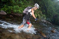 Participante que vadeia através do rio na raça imagem de stock
