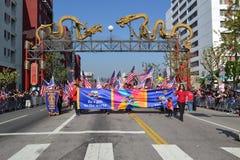 Participantes con las banderas americanas durante el 117o dragón de oro Imagen de archivo libre de regalías