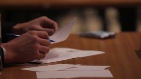 Participantes de evaluación del jurado en la competencia de deportes, haciendo notas en papeles metrajes