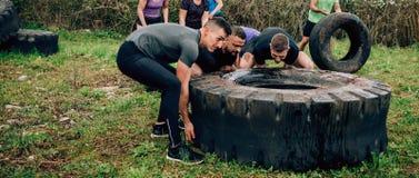 Participantes em um curso de obstáculo que gerencie uma roda imagem de stock