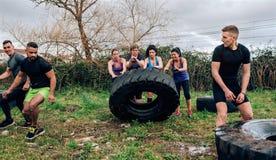 Participantes fêmeas em um curso de obstáculo que gerencie uma roda fotografia de stock royalty free