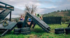 Participantes na parede de escalada do curso de obst?culo imagem de stock royalty free