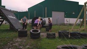 Participantes nas rodas de arrasto de um curso de obst?culo video estoque