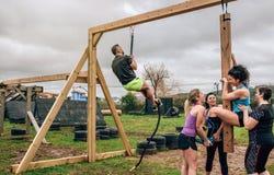 Participantes no curso de obstáculo que faz o pegboard e a corda foto de stock