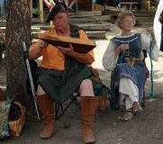 Participantes que llevan la ropa típica que canta y que juega durante el festival anual del renacimiento en Colorado imagen de archivo