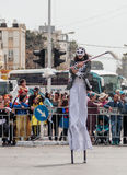 Participants at сarnival on stilts are walking along the street Royalty Free Stock Image