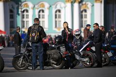 Participants of the biker movement of St. Petersburg with their motorcycles on the background of the Hermitage building royalty free stock photo