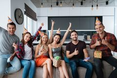 Participants in the birthday party make a group photo. They are sitting on a couch. royalty free stock images