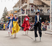 Participants at carnival on stilts are walking along the street Stock Photography