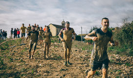 Participants in a extreme obstacle race running Stock Photo