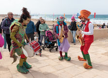 Participants of festival dressed as clowns playing musical instr Royalty Free Stock Images