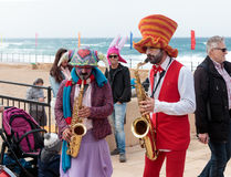 Participants of festival dressed as clowns playing musical instr Stock Photo