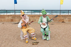 Participants of festival dressed as clowns playing stringed inst Stock Images