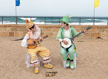 Participants of festival dressed as clowns playing stringed inst Royalty Free Stock Images