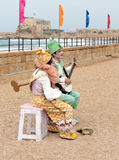 Participants of festival dressed as clowns playing stringed inst Stock Image