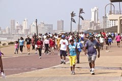 Participants of Heritage Day Walk at Durban Beachfront South Afr. DURBAN, SOUTH AFRICA - SEPTEMBER 24, 2014: National Heritage Day walk participants walk along stock image