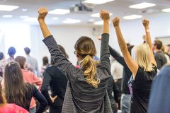 Participants of interactive motivational speech feeling empowered and motivated, hands raised high in the air. royalty free stock image