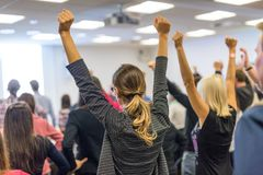Participants of interactive motivational speech feeling empowered and motivated, hands raised high in the air. Life coaching symposium. Speaker giving royalty free stock photo