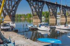 Participants of the local yacht-club anchorage near an arched bridge working with lifting sailboats to water Stock Photos
