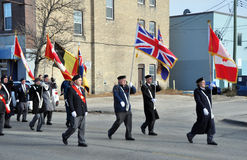 Participants of the parade with flags on the street. Photo was taken during Canadian Remembrance Day ceremonies in Winnipeg City, Manitoba province, Canada. on stock images