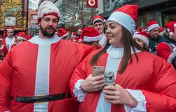 Participants of Santacon event in London. London, UK - December 2018 : Two friends dressed in fat santa outfits posing for photograph while taking part in a stock photo