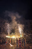 Participants of  traditional spectacle Correfocs (fire runs) with lighting fireworks. Royalty Free Stock Photo