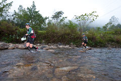 Participants wading through river in race Royalty Free Stock Image