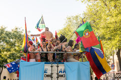 Participating dancing during the parade, moving the flags around Stock Photo