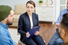 Participating in Group Therapy Session. Group therapy session at full speed: attractive young psychologist listening to male patient with concentration and royalty free stock images