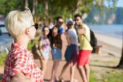 Participation blonde de femme de point de vue de l'homme, groupe de personnes marchant en parc de palmier sur la plage parlant, a Images libres de droits