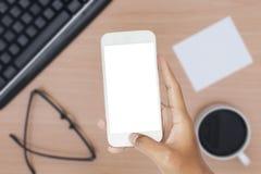 Participation de main de smartphone avec des articles de bureau photo stock