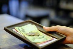 Participation en gros plan de main de billet avec le billet de banque et les pièces thaïlandais d'argent photo libre de droits