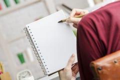 Participation et écriture de femelle en bloc-notes en spirale Image stock