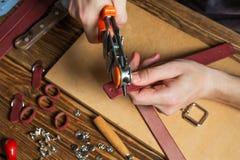 Participation principale une perforatrice et un morceau de cuir Sur la table en bois brune a dispersé avec des outils et des acce Photo stock
