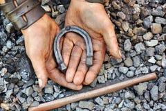 Particolare delle mani sporche che tengono ferro di cavallo Fotografie Stock