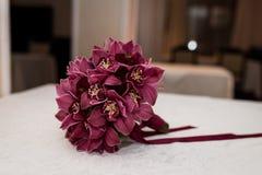 Particolari di cerimonia nuziale Mazzo nuziale delle orchidee rosse con il nastro rosso Fotografie Stock