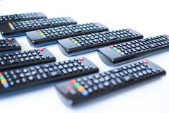 Particolarmente telecomandi neri molto vaghi per la TV su un fondo bianco fotografia stock