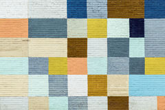 Particoloured squares painted on a brick wall Stock Images