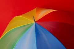Particoloured umbrella on red background. Very big umbrella to protect from rain and sun stock photos