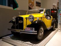 A particular 500. Detail of a yellow small car equipped with a FIAT 500 engine shown at the small museum dedicated to the italian hatchback Stock Photography