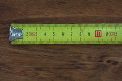 Particular of a meter tool. A flexometer on the wood royalty free stock photography