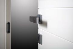 Particular open white door. Open white door on gray background stock photos