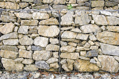 Particular of the retaining wall gabion. Retaining drywall, built of stone filling a container made from a wire mesh hexagonal mesh, said gabion Stock Images